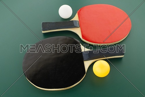 Red and black table tennis racks with a white and an yellow ping pong ball on green background