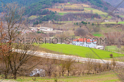 Scenic view of mountainous valley with country houses and bright green spring grass surrounded with forested hills in countryside, Mudurnu, Bolu, Turkey