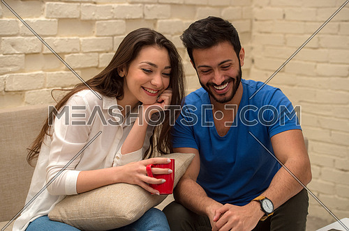 A young man and young lady sitting at home using a laptop