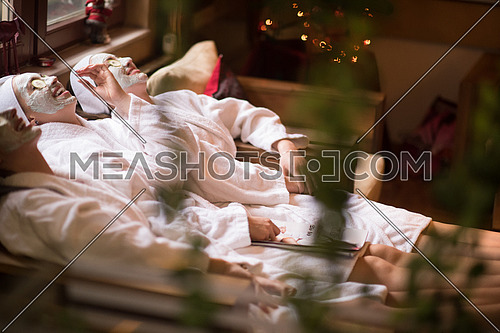 beautiful young women  getting facial clay mask at spa, lying with cucumbers on eyes