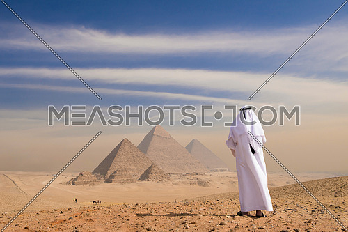 young man as tourist wearing arabian gulf traditional clothes in egypt with giza pyramids in background