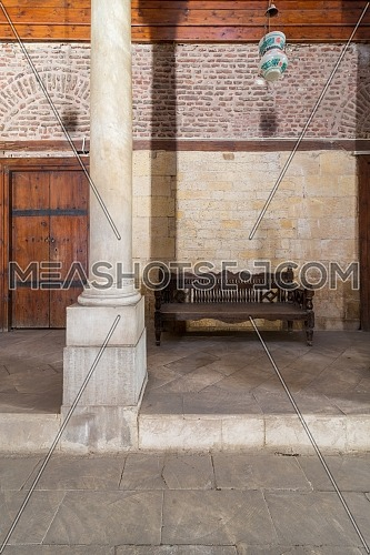 Stone bricks wall and aged wooden couch at the main hall of historic Mamluk era Beshtak Palace - Qasr Bashtak, located in Bayn al-Qasrayn (between the two palaces) area, Muizz Street, Cairo, Egypt