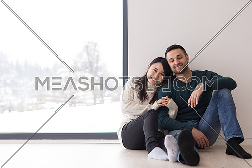 happy young multiethnic couple sitting near window at home on cold winter day