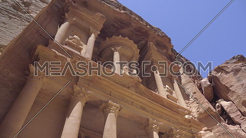 Left pan reveal of the upper portion of the Treasury facade in Petra