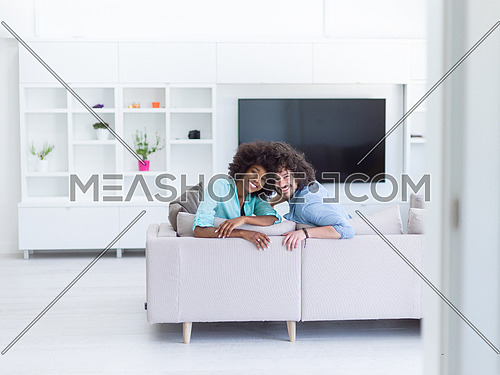 Young multiethnic couple sitting on a sofa in the luxury living room