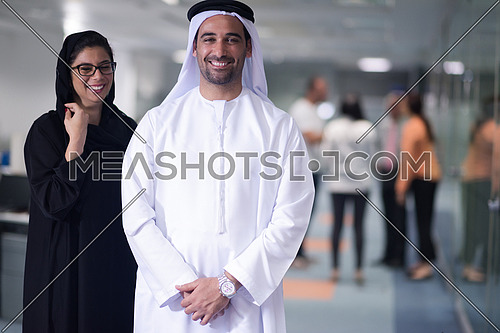 arabian famale and male business people standing as team in modern office with group of people in background