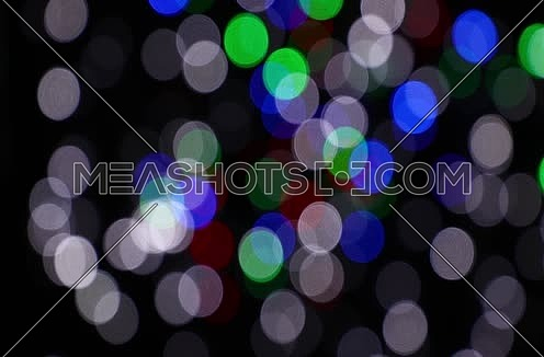 Colorful multicolor festive Christmas circular bokeh over dark, white, blue, green and red lights slow moving trembling and shaking