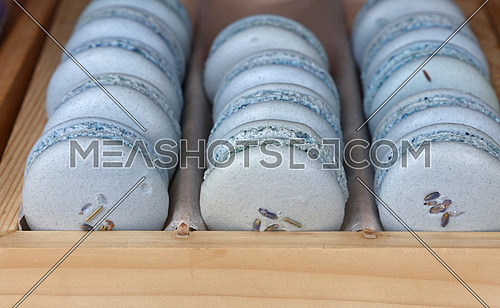 Fresh baked lavender blue macaroon pastry cookies (macarons, macaroni) in wooden box of retail store display, close up, high angle view