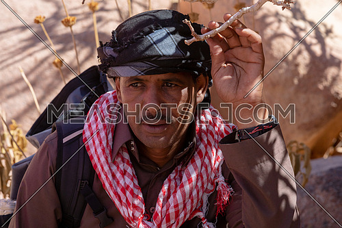 Close up shot for bedouin male get rest in the shade besides Almond tree with bedouin guide to explore Sinai Mountain for wadi Freij at day.