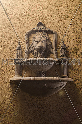 water well on the wall contain a head of a lion with two human figures statues