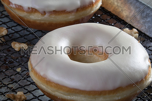 top side view  of white glazed donuts with walnuts aside, hazelnuts