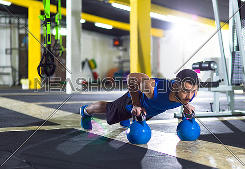 Young strong man doing pushups on kettlebells at cross fitness gym