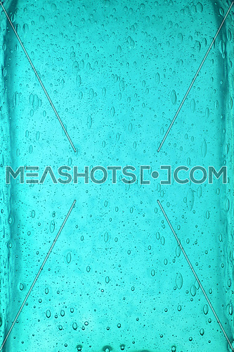 Background texture of solid transparent teal blue color glass with pattern of air bubbles, close up