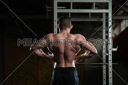 Young Man Standing Strong In The Gym And Flexing Rear Lat Spread Pose - Muscular Athletic Bodybuilder Fitness Model Posing Exercises