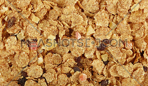 Breakfast granola muesli with dried fruits close up pattern background, elevated top view