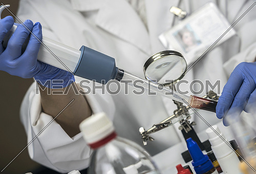 Specialized police taking shows blood in microscope holder to analyze in scientific laboratory, conceptual image