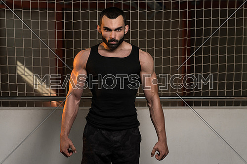 Portrait Of A Young Fit Man Showing His Well Trained Body In Tank - Muscular Athletic Bodybuilder Fitness Model Posing After Exercises