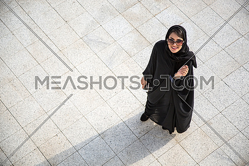 Happy saudi lady looking up