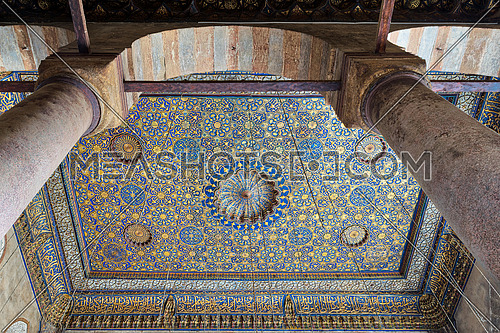 Ornate ceiling with blue and golden floral pattern decorations framed through huge arch and two columns at Sultan Barquq mosque, Al Moez Street, Old Cairo, Egypt