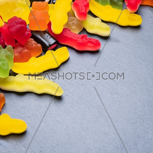 Many colored candies on dark background. Top view with copy space for your greetings,square photo.