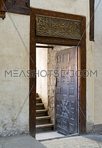 Wooden aged decorated door and beige plaster wall leading to stone staircase, Medieval Cairo, Egypt