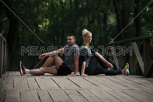 Young Couple Stretching Before Running In Wooded Forest Area - Training And Exercising For Trail Run Marathon Endurance - Fitness Healthy Lifestyle Concept