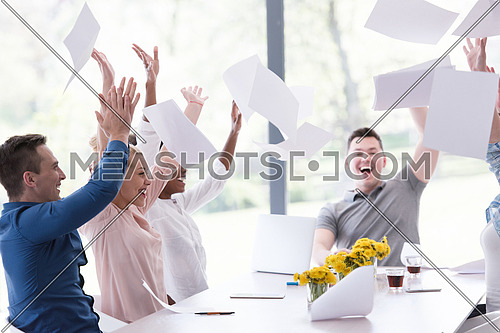 multiethnic Group of young business people throwing documents and looking happy while celebrating success at their working places in startup office