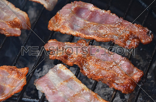 Seceral crispy smoked grilled barbecue bacon slices, cooked on bbq smoke grill, close up