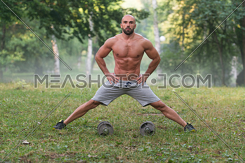 Young Muscular Athlete Doing Stretching With Dumbbbells As Part Of Bodybuilding Training - Outdoors Workout - Sports And Fitness - Concept Of Healthy Lifestyle - Fitness Male