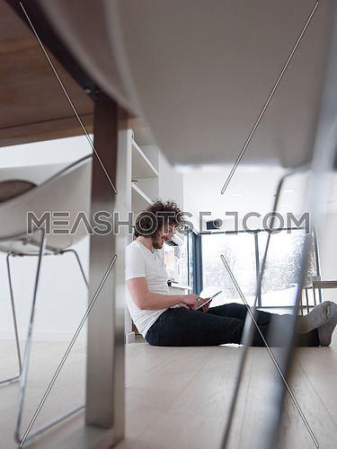 Handsome casual young man using a tablet at home