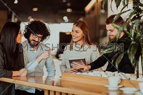 A group of people on a coffee break use laptops, tablets and smartphones while talking in new business projects