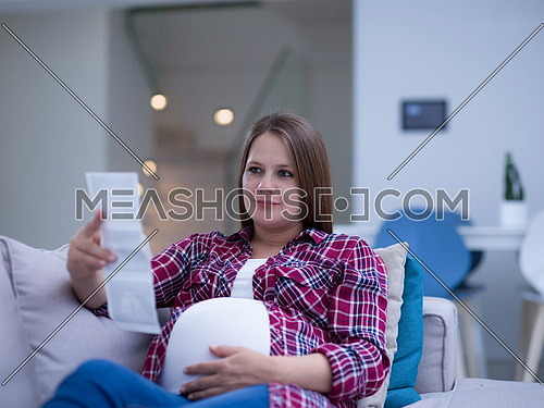 Young pregnant woman looking baby's ultrasound photo while relaxing on sofa at home