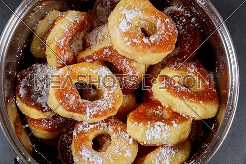 Homemade berliner donuts on plate with sugar and its ingredients in bowl