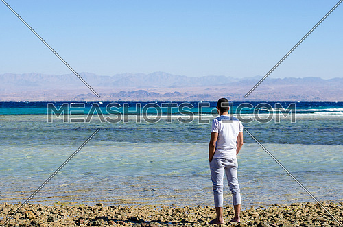 A man standing by the beach looking towards the horizon