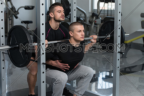 Personal Trainer Showing Young Man How To Train Barbell Squats Exercise In A Health And Fitness Concept