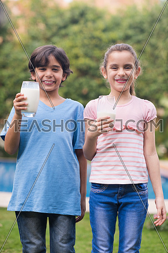 Middle Eastern boy and girl enjoying with a glass of milk in their hands outside on summer day
