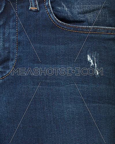 Dark indigo blue washed cotton jeans denim texture background with front pocket, close up