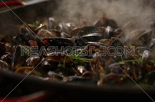 Cooking steamed and roasted Belgian mussels with herbs at big frying pan, close up, low angle view