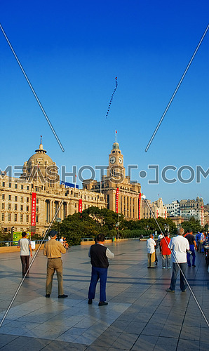 old people flying a kite on the shanghai bund at sunrise