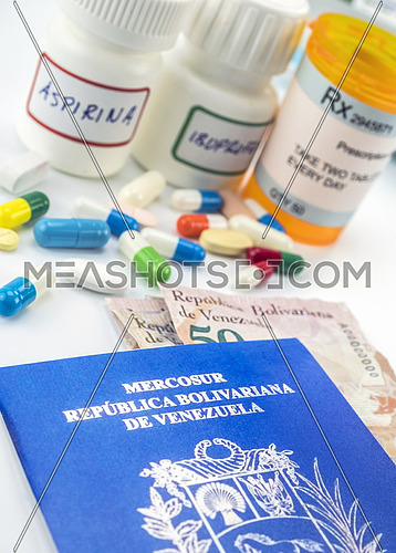 Medicines next to banknotes and passport of Venezuela, shady deal of medication in full crisis of country of Latin America, conceptual image, composition vertical