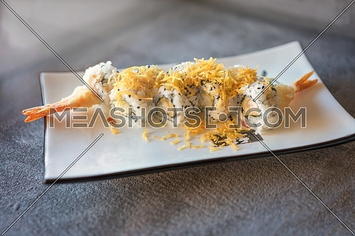 shrips sushi served on rectangular white plate on dark gray stone background