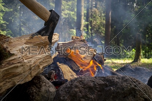 Camp fire in a forest with chopper lodged in a log of wood in the foreground in a healthy active lifestyle concept