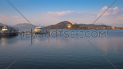 In the picture boats and yachts moored at the port of Arona, Maggiore Lake and in the background the fortress of Angera.