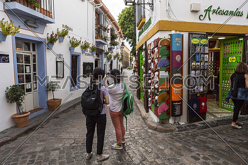 CORDOBA, SPAIN - September, 27, 2015: Two young girls take photo in the Romero street, jewish quarter in Cordoba, Cordoba, Spain