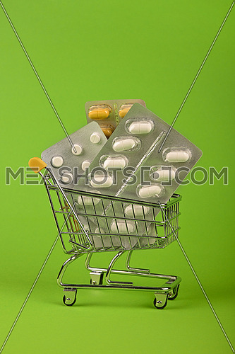 Close up several different blister packs of pills in small shopping cart over green background, concept of online medicine order delivery, low angle view