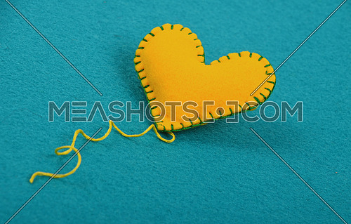 Felt craft and art, one handmade yellow stitched toy heart with thread on blue background, low angle view, close up