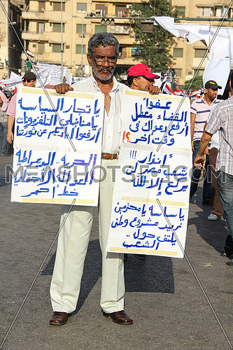 a man holding signs in tahrir square