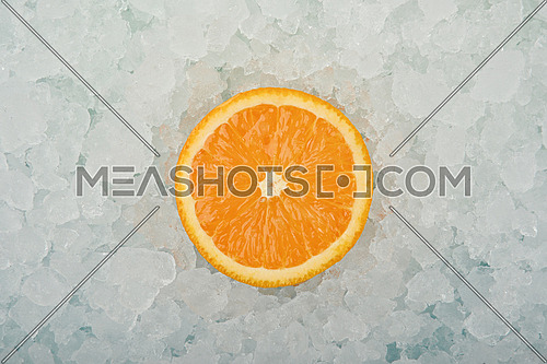 Close up one fresh juicy orange cut half slice over background of crushed ice, elevated high angle view, directly above