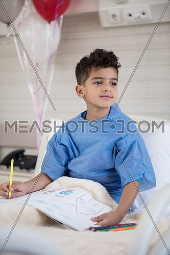 little middle eastern boyl painting home and family at hospita bed in a large modern hospital