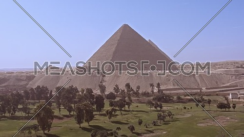 Fly over shot for The Great Pyramid of Khufu from Green field in background in Giza at day